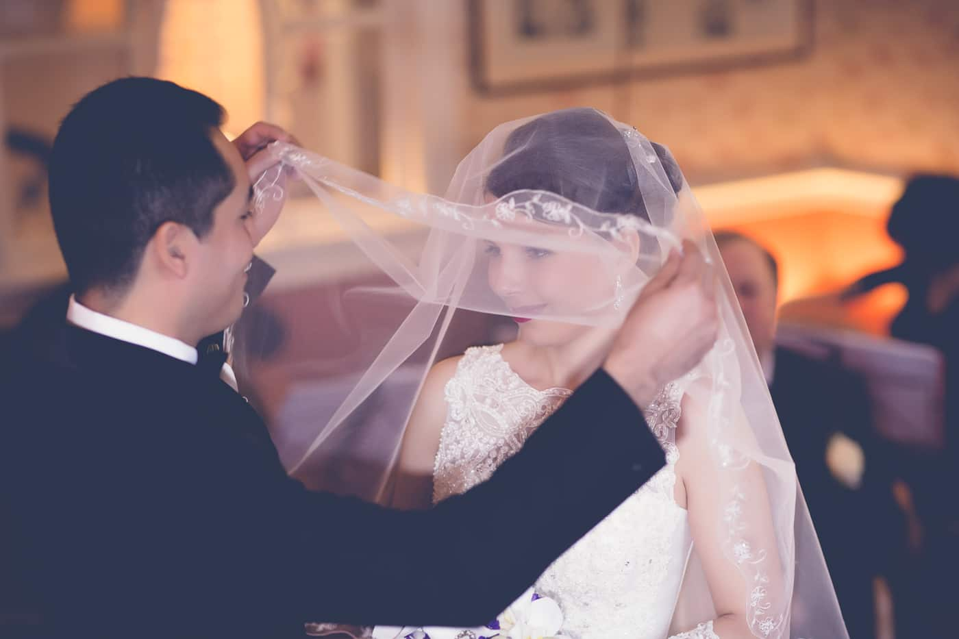 The groom is lifting her veil during the ceremony