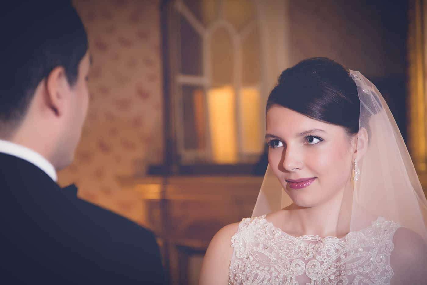 The bride is emotionally looking at her groom during the ceremony
