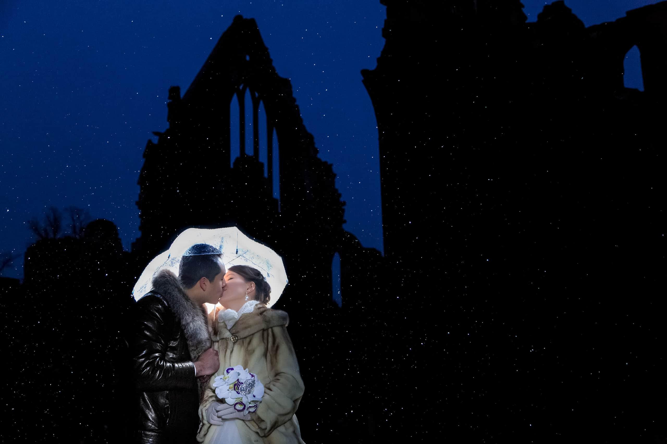 Bride an groom kissing under snowflakes