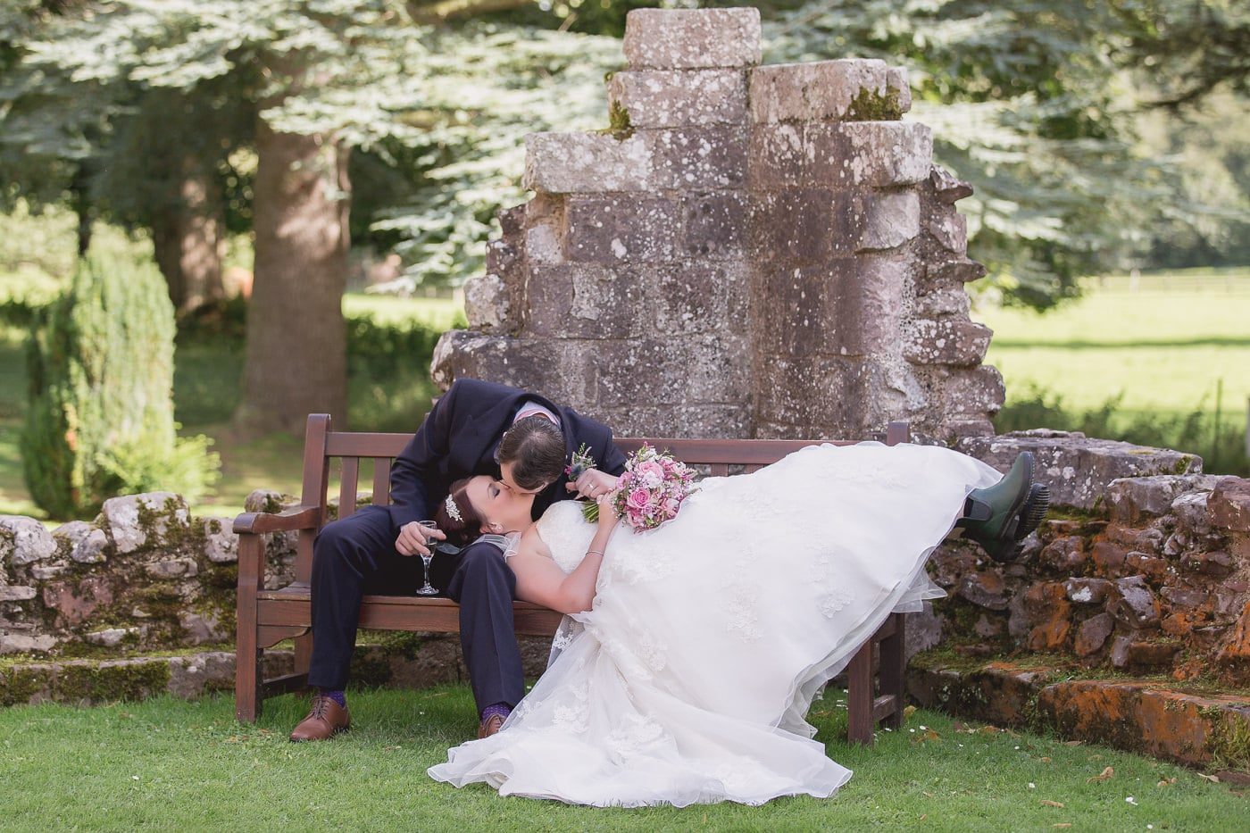 The groom is kissing the bride in the garden