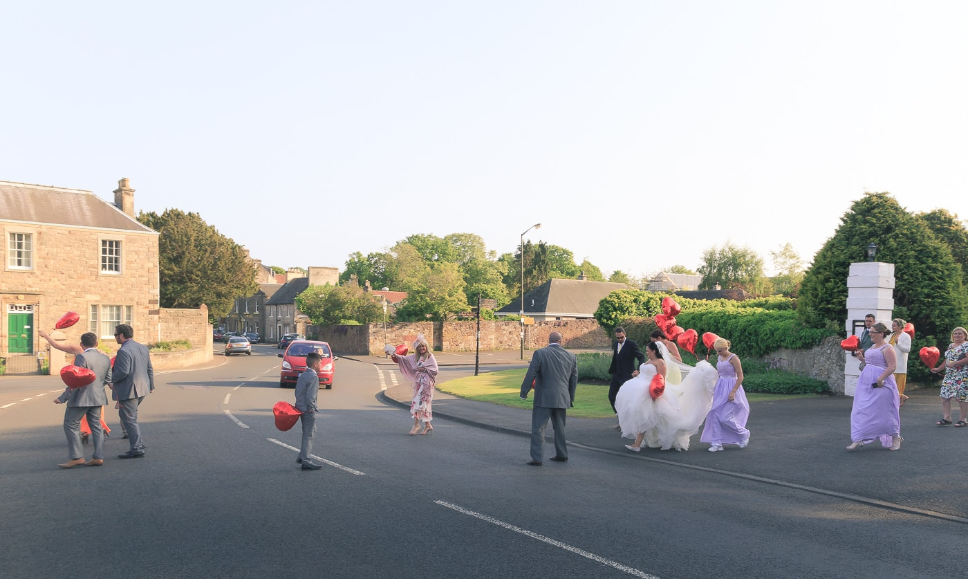 The bridal party is crossing the street