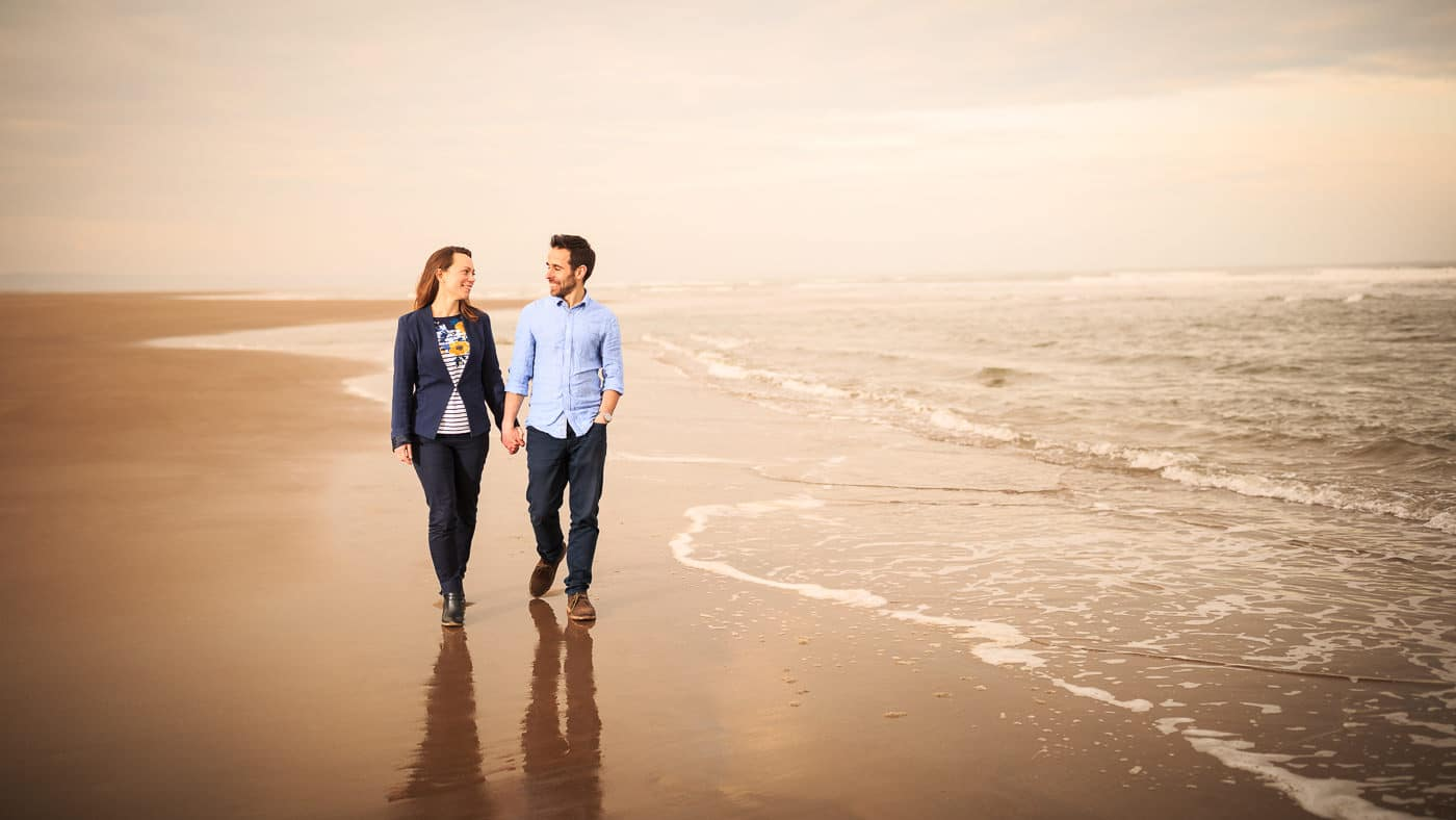 The couple is walking on the beach