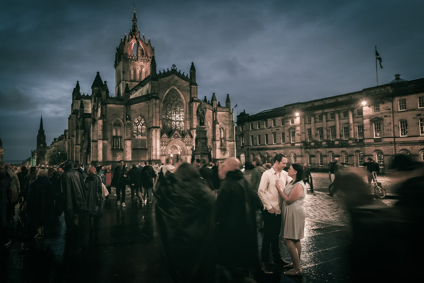 The couple stands in the middle of the crowd in front of St Giles Cathedral