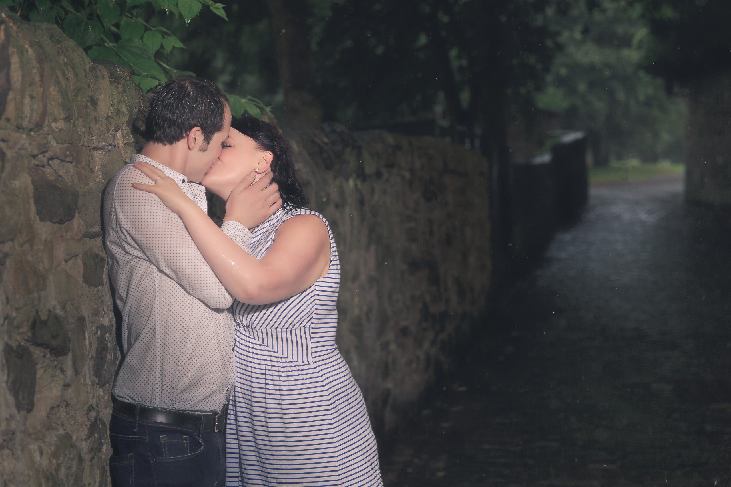 The couple is kissing on a street of edinburgh