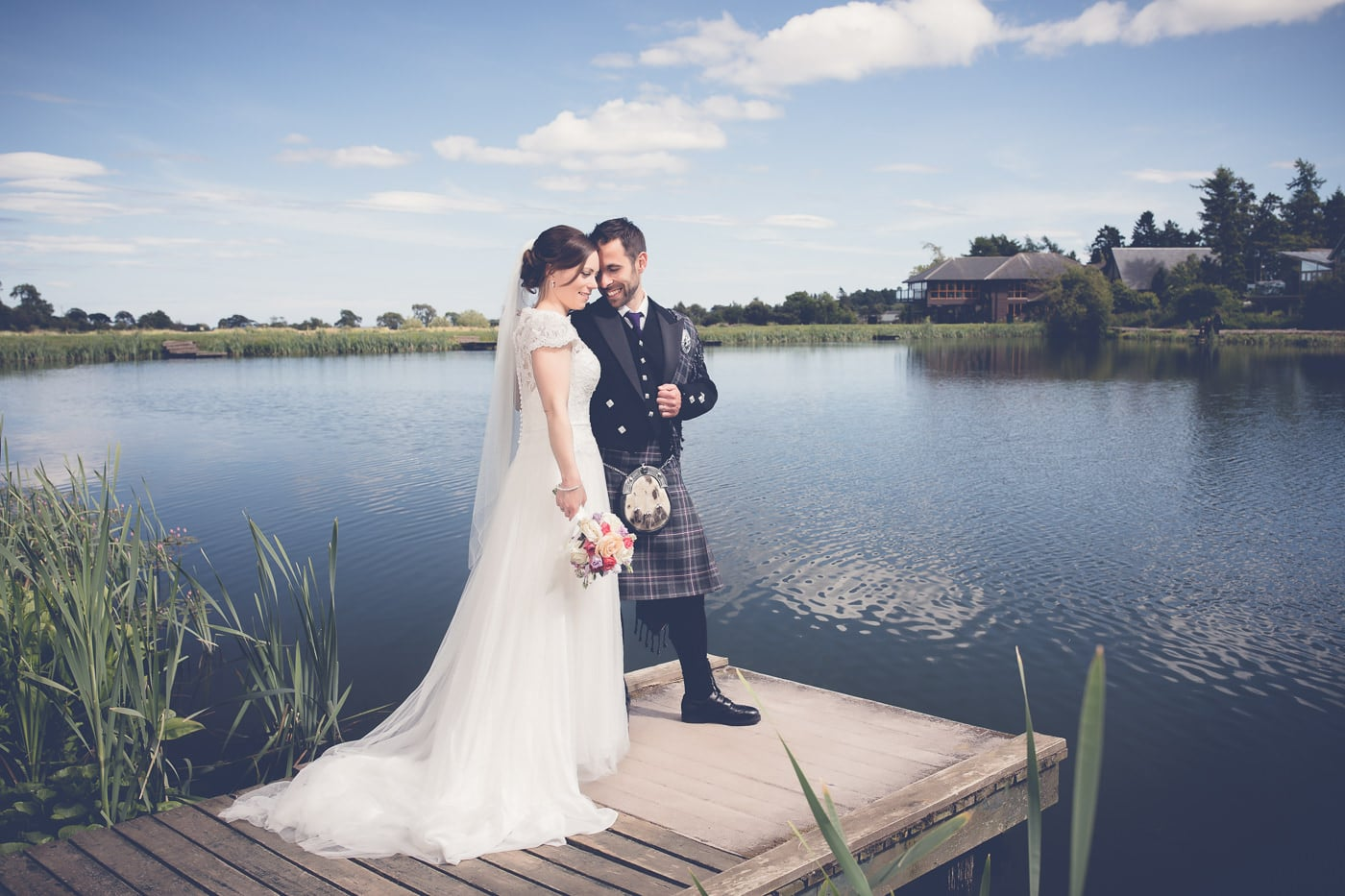 Bride and groom near a pond at the Forbes of Kingenny near Dundee Scotland
